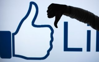 ILLUSTRATION - A woman makes the 'thumbs down' sign with her fist and thumb in front of an enlarged 'Like' symbol of the social netweorking site Facebook in Schwerin, Germany, 04 April 2013 (STAGED PICTURE). The social network counts more than 25 million users in Germany alone, but it keeps losing more and more especially young users to other online services. Photo: Jens Buettner